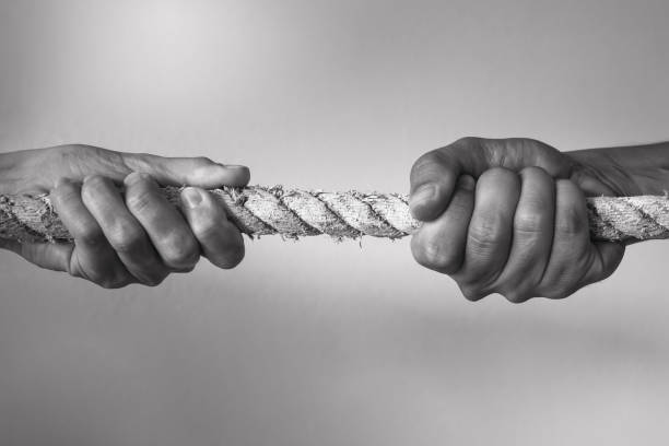 Hands pulling rope playing tug of war stock photo