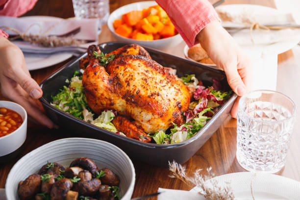 Hands put a dish with whole roasted chicken on a festive table. The concept of family dinner or Thanksgiving celebrate stock photo
