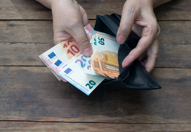 Hands put banknotes 10, 20, 50 euros in a black wallet on a wooden background. Poverty or wealth concept stock photo