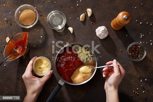 istock Hands put mustard in the saucepan for cooking bbq sauce. 936987720