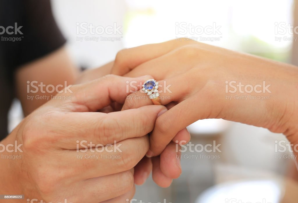 Hands putting on wedding ring. stock photo