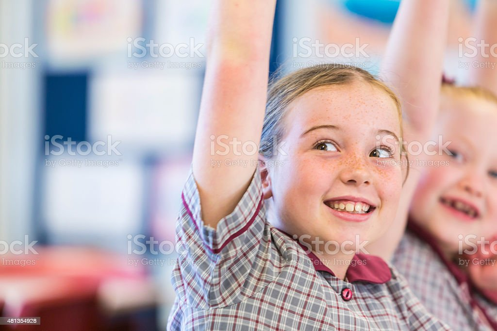 Hands Raised Smiling School Girls in the Classroom stock photo