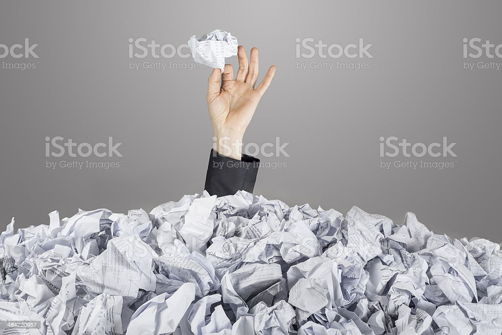 Hands reach out from big heap of crumpled papers stock photo