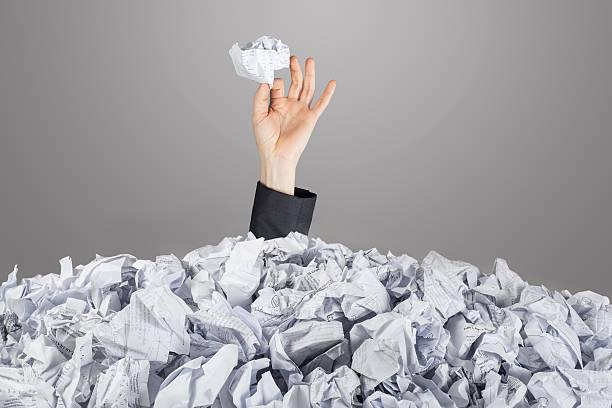 hands reach out from big heap of crumpled papers - gömülü stok fotoğraflar ve resimler