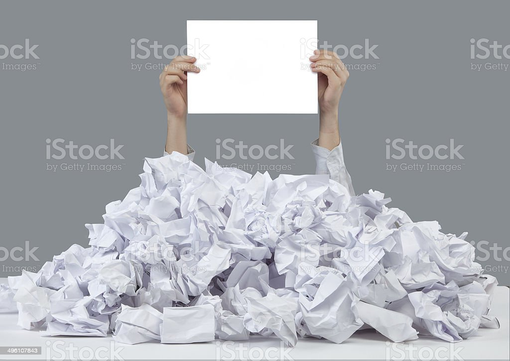 Hands reaches out from big heap of crumpled papers stock photo