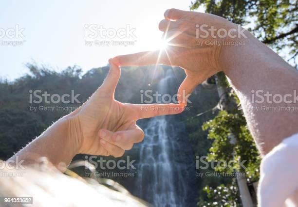 Foto de Mãos Atingindo Até A Cachoeira De Quadro Na Floresta Tropical e mais fotos de stock de 55-59 anos