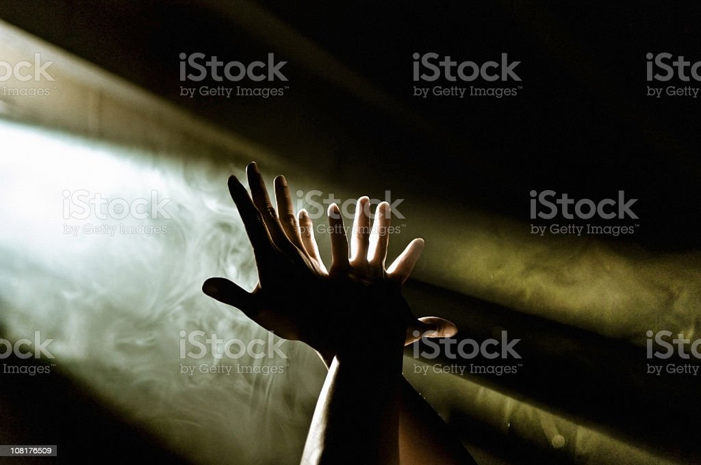 Hands Reaching Up to Ray of Light stock photo