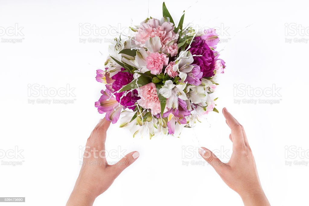 Hands receiving a pastel bouquet from pink and purple gillyflowe stock photo