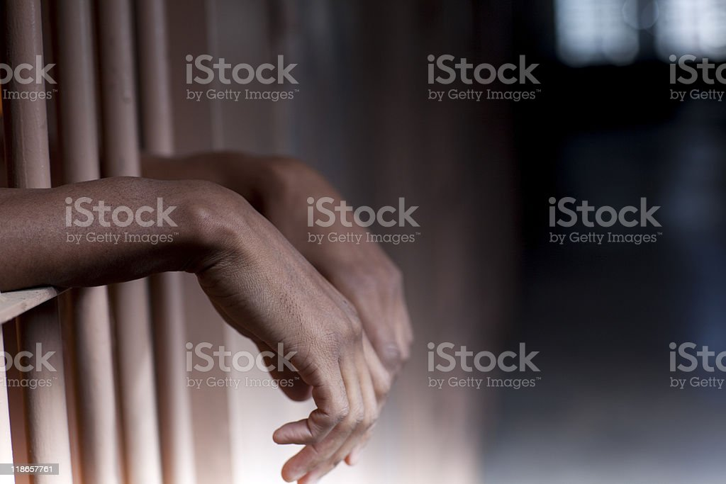 Hands resting on prison bars in a forlorn pose stock photo