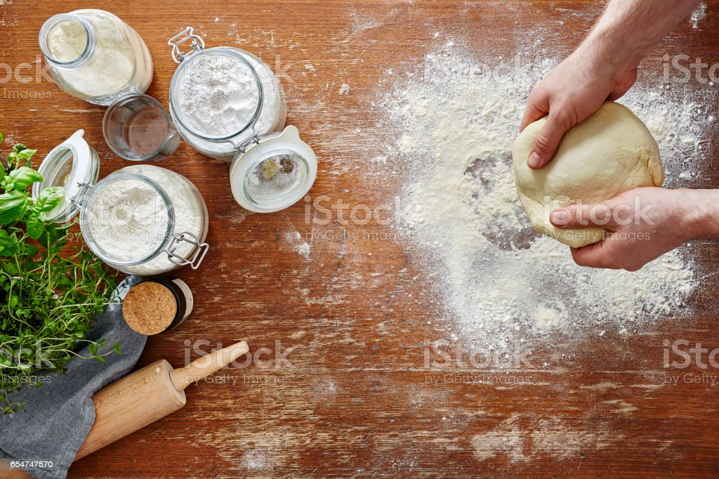 hands rolling out dough atmospheric kitchen scene flour and wooden workspace stock photo
