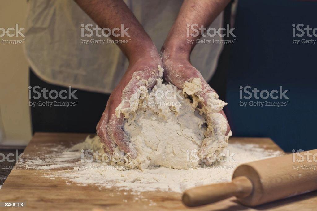 Hands rumple dough in kitchen stock photo