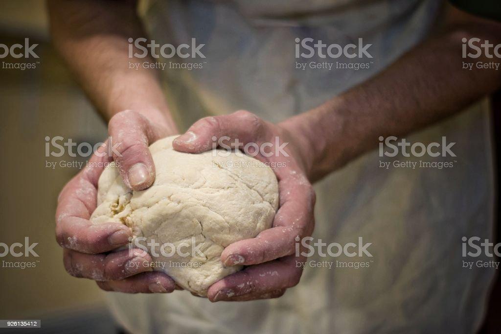 Hands rumple dough in kitchen.Defocus in the background. stock photo