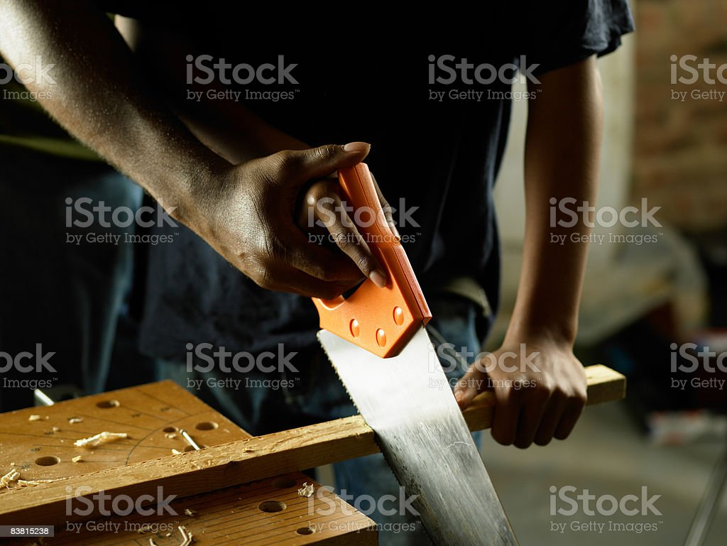 Hands sawing wood royalty-free stock photo