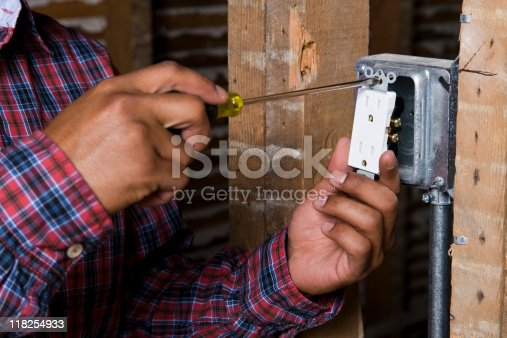Portrait of a tan young adult latino male construction worker wearing a plaid red and blue long sleeve shirt screwing in an electrical outlet into the metal mainframe.
