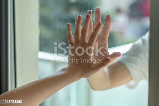 Hands separated by a glass window for social distancing during the corona virus lockdown
