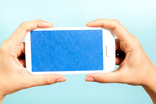 istock Hands showing a blue horizontal mobile phone concept on blue background 478493341