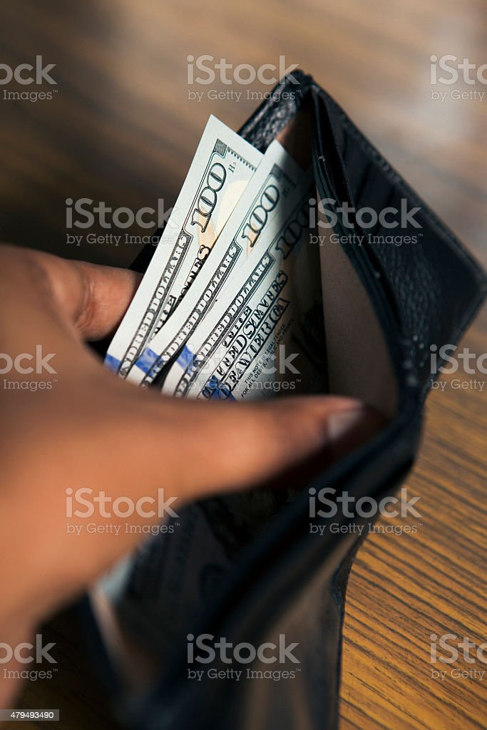 Hands showing money inside a wallet.
