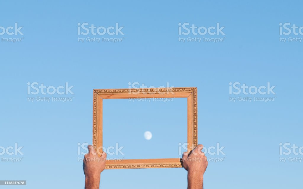 Hands showing moon in wooden frame