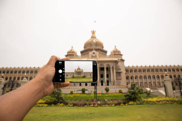 Hands showing of taking a picture of Vidhana soudha with mobile phone. Hands showing of taking a picture of Vidhana soudha with mobile phone taken on mobile device stock pictures, royalty-free photos & images