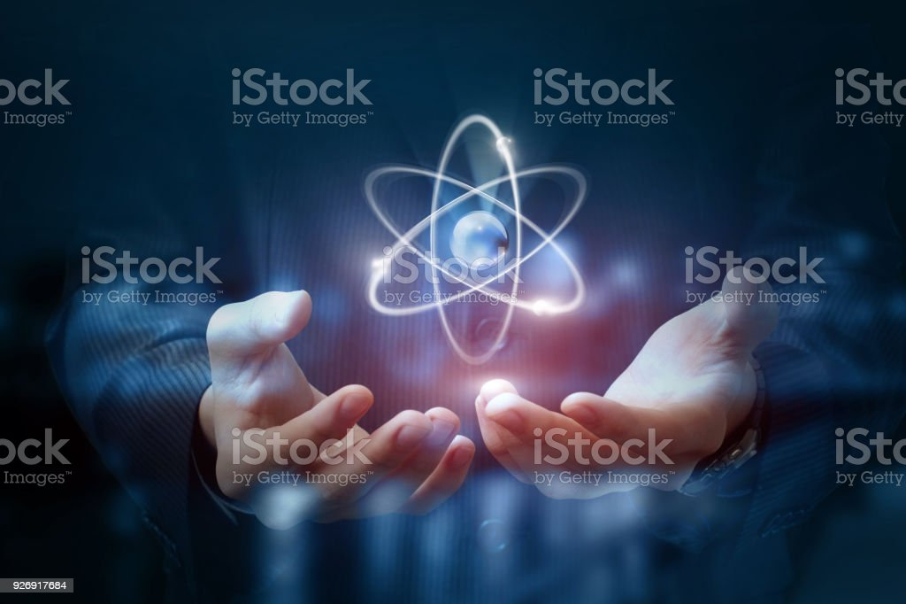 Hands shows the atom . stock photo