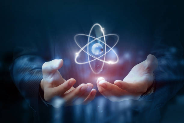 Hands shows the atom . Hands shows the atom on a dark blurred background. radioactive contamination stock pictures, royalty-free photos & images