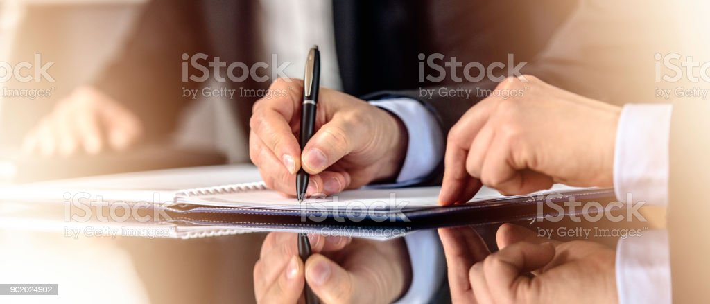 Hands signing document stock photo