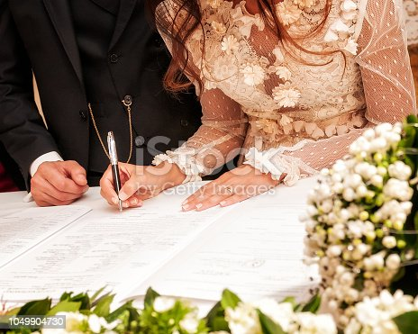 Detail of the hand of a bride who signs the marriage act