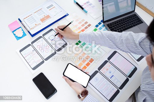 Hands sketching of screens for mobile responsive website development with UI/UX. Developing wireframe sketch layout design mockup on smartphone screen.