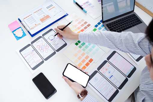 istock Hands sketching of screens for mobile responsive website development with UI/UX. Developing wireframe sketch layout design mockup on smartphone screen. 1093434430