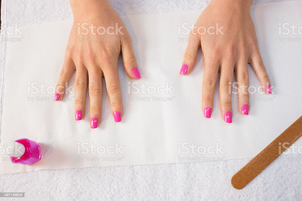 Hands spread out on manicure table showing pink nails at the nail...