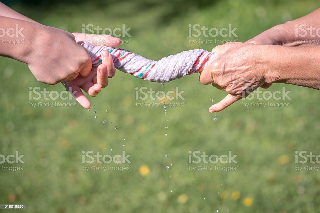 Hands squeeze wet fabric stock photo