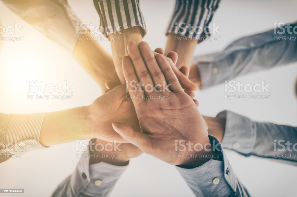 Hands stacked in a pile. A symbol of teamwork and trust. - foto stock