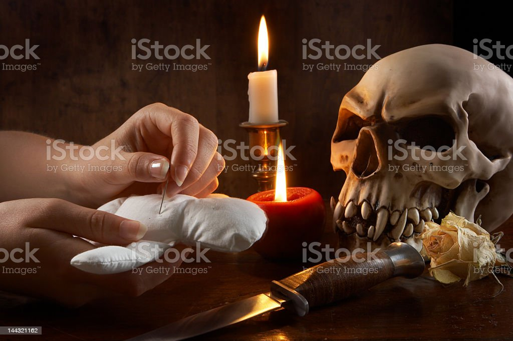 Hands sticking a pin into a voodoo doll by a skull and knife stock photo