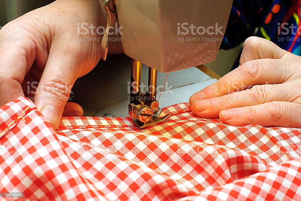 Hands stitching denim cloth with a sewing machine stock photo