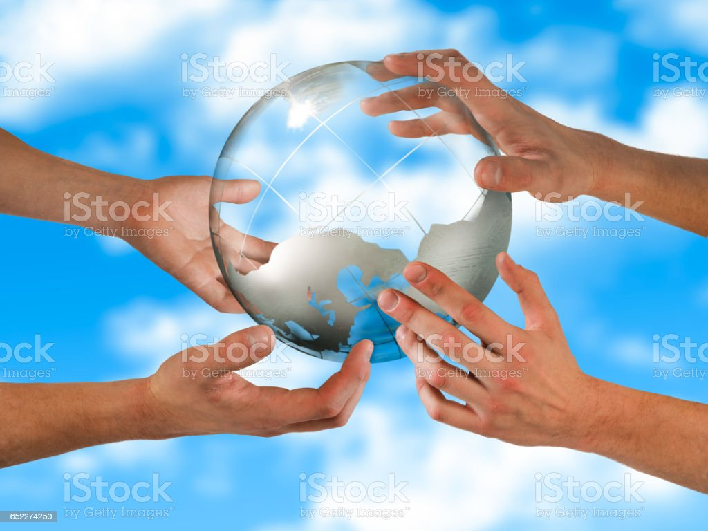 Hands supporting a transparent globe. The background of blue sky stock photo