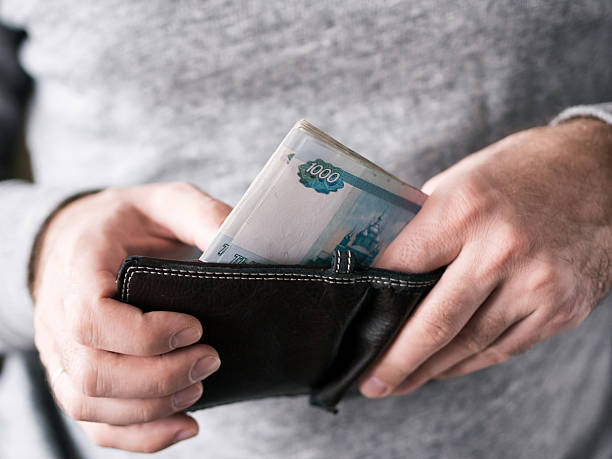 Hands take out russian rubles from wallet Hands take out russian rubles from wallet. Closeup on a man's hands as he is getting a banknote out of his wallet eastern european descent stock pictures, royalty-free photos & images