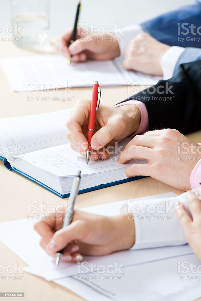 Hands taking notes with ballpoint pens royalty-free stock photo