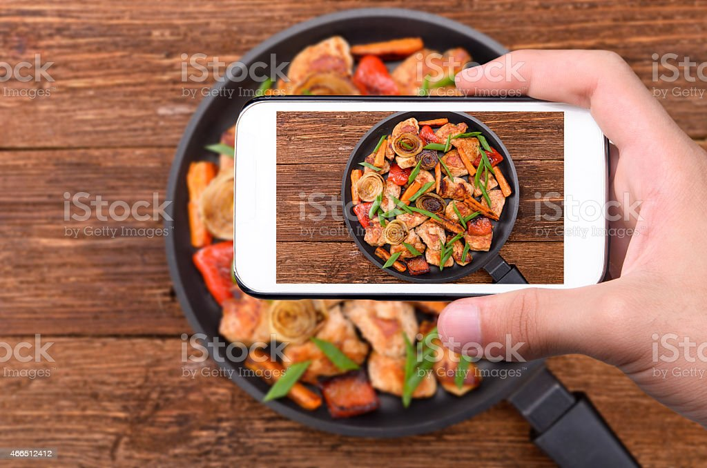 Hands taking photo meat with vegetables with smartphone. stock photo
