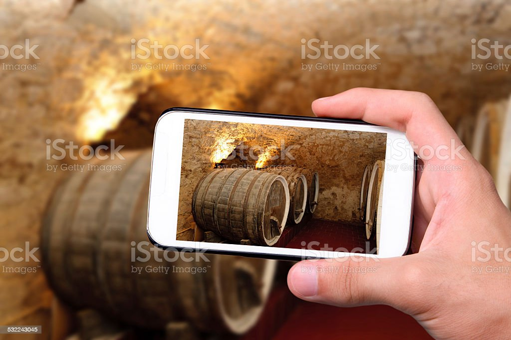 Hands taking photo old wine barrels with smartphone. stock photo
