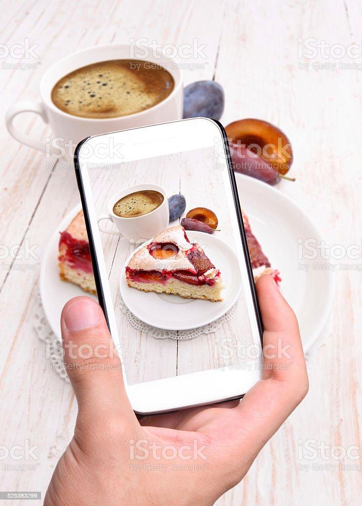 Hands taking photo plum cake with smartphone. stock photo