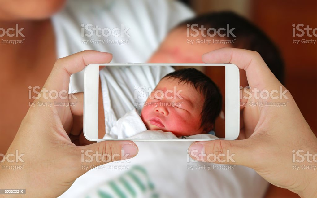 Hands taking picture of Newborn baby with smartphone.