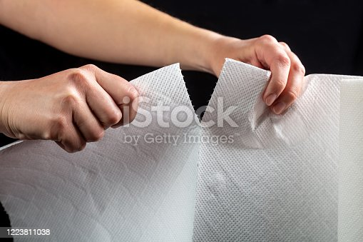 istock Hands tear off a piece of white paper towel from a roll on a black background. Horizontal orientation 1223811038