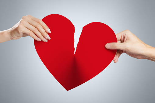 istock Hands tearing a red heart 1183356280