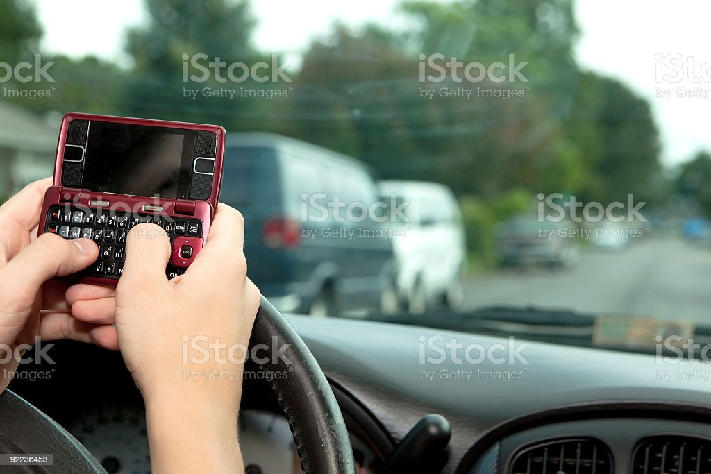 Hands texting over a steering wheel while driving royalty-free stock photo