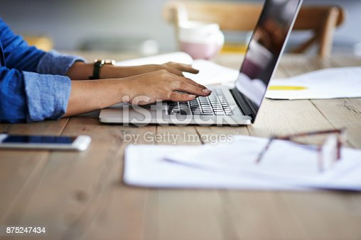 Cropped shot of a woman using a laptop while working from home