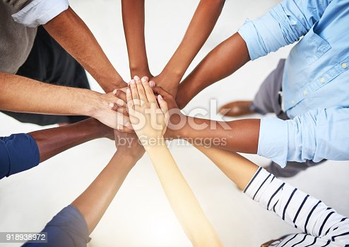 Cropped shot of a group of businesspeople joining their hands in solidarity