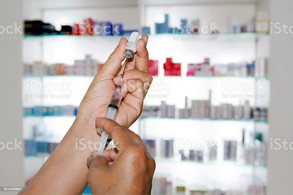 Hands the doctors filling a syringe on store medicine stock photo