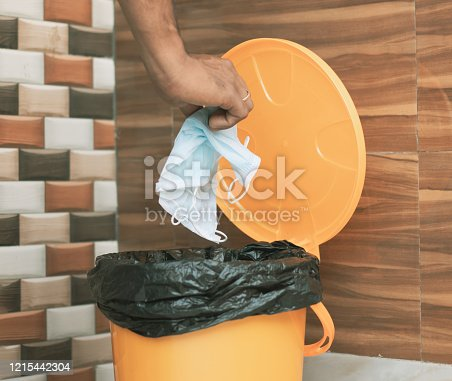 Hands throwing medical mask into closed bin - Covid-19, Coronavirus advice to discard or dispose medical mask to closed trash can after usage - concept showing to do hygiene practice
