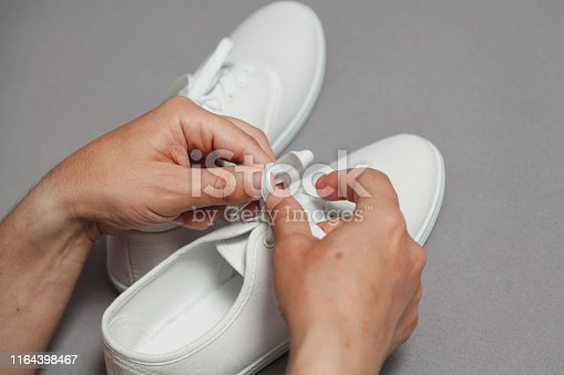 Tanned hands tie shoelace on white sneaker against gray background close up