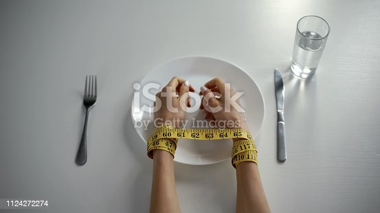 istock Hands tied with tapeline on empty plate, girl obsessed with counting calories 1124272274
